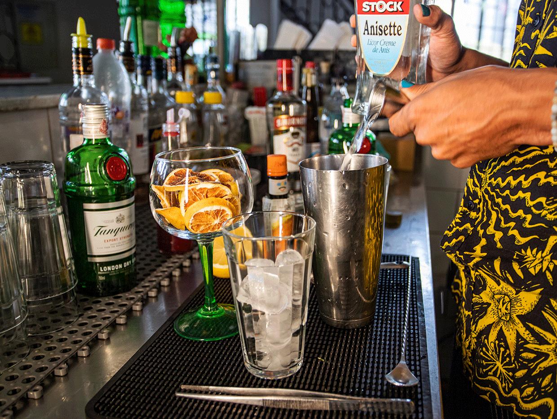 Fotografia em ambiente interno. No centro da imagem há as mãos do bartender Raul colocando Gin dentro de copo de metal. Ao fundo da fotografia, há 15 garrafas de bebidas alcoólicas, seis copos limpos e algumas colheres.