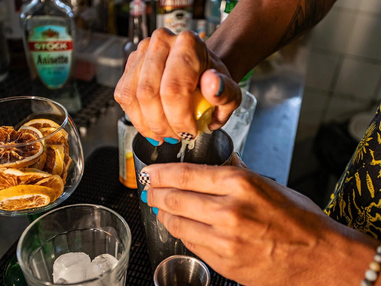 Fotografia em ambiente interno. No centro da imagem, Raul espreme uma laranja dentro de um copo.